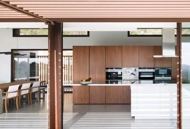 ??  ?? Oben Über die Terrasse gelangt man in die offene Wohnküche mit großem Kochfeld und multifunktionaler Arbeitsfläche. Mitte Die dynamische Pendelleuchte Rhythm by Vibia greift perfekt die Optik der Holzstrukturen vom Sonnenschutzdach auf.