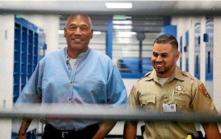 ?? PHOTO: REUTERS ?? OJ Simpson is escorted by a corrections officer as he arrives for his parole hearing at Lovelock Correctional Centre in Lovelock, Nevada.