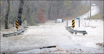 ?? ALEXA WELCH EDLUND/TIMES-DISPATCH ?? The Newfound River flooded Coatsville Road in Hanover County as a result of near-record amounts of rain that fell Thursday.