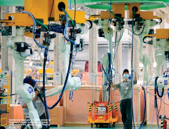 ??  ?? Technicians fine tune a robotic system at Tangshan Kaiyuan Autowelding System company in north China's Hebei Province on July 17