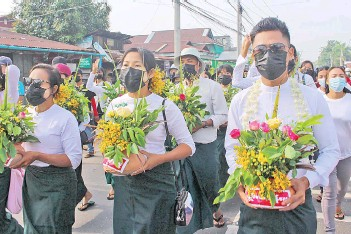 ?? — AFP photo ?? Protesters carrying pots filled with Thingyan festival flowers and leaves during a demonstration against the military coup in Dawei.