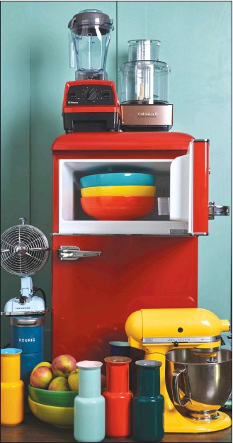 ?? Associated Press photo ?? This photo provided by Katie Workman shows a variety of kitchen items in different colours, including a red fridge, a yellow stand mixer and some brightly coloured bowls and vases, in a New York kitchen. There are a lot of ways to add colour to your kitchen.