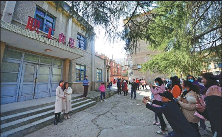 ?? XIE YONG / FOR CHINA DAILY The site ?? Film fans pose inside an old factory complex in Xiangyang, Hubei province, that was featured in the current blockbuste­r Hi, Mom. has quickly become a popular tourist attraction.