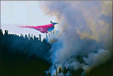 """?? National Parks Service ?? A PLANE drops f lame retardant in Sequoia and Kings Canyon national parks. """"We've been painting the mountains red with retardant the last couple of days,"""" said Clay Jordan, parks superintendent."""