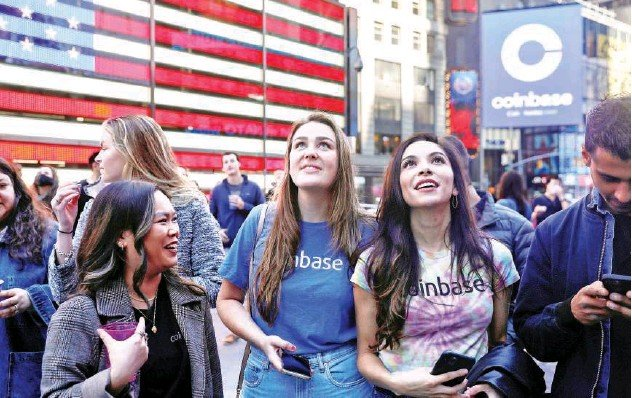 ?? Reuters ?? ↑ Employees of Coinbase Global Inc, the biggest US cryptocurrency exchange, watch as their listing is displayed on the Nasdaq at Times Square in New York on Thursday.
