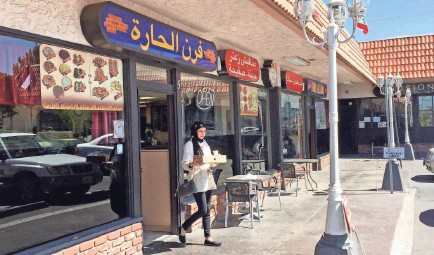 """?? GILLIAN FLACCUS/AP ?? A customer exits a Lebanese eatery in Anaheim's """"Little Arabia"""" neighborhood miles from Disneyland in Orange County. Southern California is home to the nation's largest concentration of Arab Americans."""
