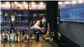 ?? Picture: Noriko Hayashi/Bloomberg ?? A bartender prepares drinks next to a screen displaying stock quotes at Stock Pickers, a tip-trading bar for investors in Tokyo, this week.