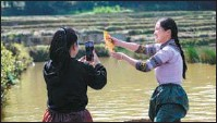 ?? LIN YIGUANG / XINHUA ?? Left: Cascading rice terraces set a majestic scene in Yuanyang county, Yunnan province. Right: Ding Ji'nan (right), a member of the Hani ethnic group, and a colleague from her new media team livestream catching fish from water on a rice terrace in Dayutang village, Xinjie town, Yuanyang.
