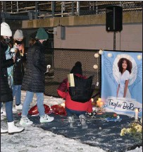 ??  ?? Candles and flowers are placed at a sign remembering the bright smile of Taylor DeRosa.