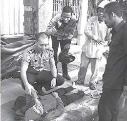 ?? POLDA JATIM FOR JAWA POS ?? SIGAP: AKBP Eddwi Kurniyanto saat menolong korban kecelakaan di Jalan A. Yani pada 8 Maret 2018 lalu.