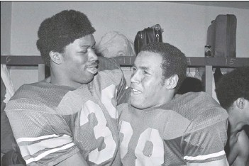?? ASSOCIATED PRESS FILES ?? Southern California fullback Sam Cunningham (left) and running back Anthony Davis embrace in the locker room after USC's 42-17 triumph in the 1973 Rose Bowl in Pasadena. Cunningham, an All-American fullback at Southern California, died Tuesday at age 71.