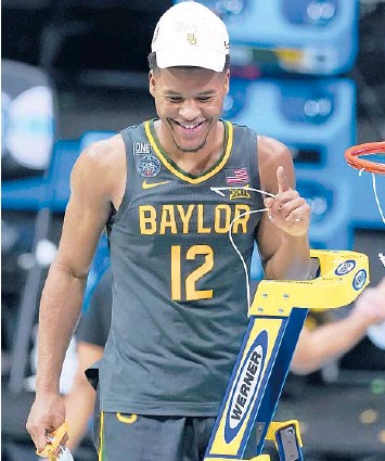 ?? DARRON CUMMINGS/AP ?? Guard Jared Butler cuts down the net after Baylor's championship win over Gonzaga on Monday night.
