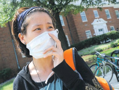 "?? ALGERINA PERNA/BALTIMORE SUN PHOTOS ?? Marnie Mitrsomwan­g, 27, a graduate student in English at the University of Maryland, College Park, leaves the Health Center; she has ""regular"" flu, she said, but not H1N1. Caution signs (below) dot the campus along with bottles of hand sanitizer."