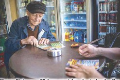 ?? AFP ?? Stoyan Stoimenov, 96, buys scratchcards at a local coffee shop in the village of Tsurkva, near the Bulgarian capital of Sofia, in May.