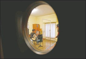 ??  ?? Carlo D'Ariano is seen through a window as he plays his guitar behind a transparent panel during a lesson with maestro Maria Vittoria Jedlowski.