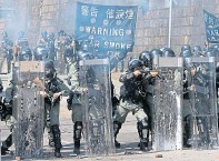 ??  ?? Hong Kong riot po­lice pre­pare to fire on protesters
