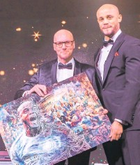 ??  ?? Justin Eagleton presenting a piece of his art to Manchester City captain Vincent Kompany at a gala dinner