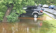 ?? ERIC ASPENSON / MILWAUKEE JOURNAL SENTINEL ?? A car is parked this week in floodwaters near the Milwaukee River on Shoreland Parkway in Mequon.