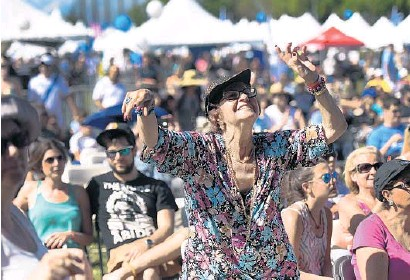 ?? PHOTOS BY JIM RASSOL/STAFF PHOTOGRAPHER ?? Charita Cooper, of Aventura, dances to live music as she celebrates Israel at C.B. Smith Park in Pembroke Pines. Sunday's event included live music, art and business vendor displays.
