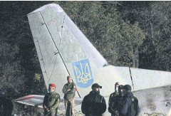 ??  ?? GRIM TOLL: Rescuers and ex­perts work on the place of The Antonov An-26 air­craft crash at Chuhuiv mil­i­tary air base about 30km south­east of Kharkiv.