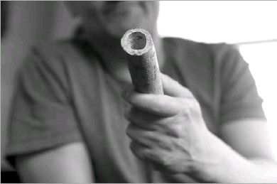 ?? Shafkat Anowar/the Associated Press ?? Troy Hernandez, an environmental justice activist, showed a piece of lead pipe obtained from his residence in Chicago's Pilsen neighborhood. He recently spent $15,000 to replace the lead service lines bringing water into his home.