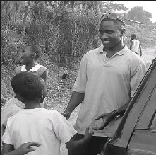?? CANADA AFRICA COMMUNITY HEALTH ALLIANCE ?? Jimmy Sebulime, above, who played basketball for the Algonquin Thunder as a student, greets children in his native Uganda. He now works for the Canada Africa Community Health Alliance, who with help from Algonquin athletic director Ron Port, provided...