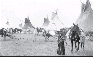 ?? Galt Archives photo 19851081000 ?? A First Nations camp is shown in 1890, with two Aboriginal women, horses, teepees and travois visible.