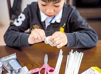 ??  ?? Akito Takahashi playing with a handmade robot kit.