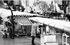 ??  ?? A worker inspects a C Series aeroplane wing in the Bombardier factory in Belfast, Northern Ireland. Britain has thrown financial support for the first time behind exports of Bombardier CSeries jets part-built by Northern Ireland workers caught up in a...