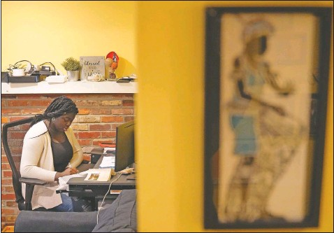 ?? (AP Photo/Matt Rourke) ?? Ebele Azikiwe, 12, writes at her desk at home in Cherry Hill, N.J. Ebele testified in October at a state Assembly hearing, lending her support to legislation requiring New Jersey's school districts to add diversity to curriculums.