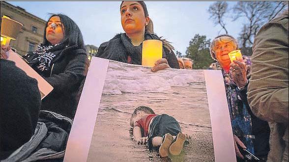 ?? CHRIS HOPKINS / GETTY ?? Una mujer sostiene una foto de Aylan durante una marcha enMelbourne para pedir al Gobierno australiano que aumente su cuota de refugiados