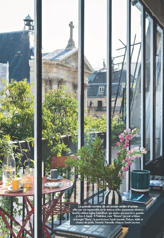 """??  ?? La grande verrière de cet ancien atelier d'artiste offre une vue imprenable sur la terrasse et les monuments alentour, dont la célèbre église Saint-Roch, qui donne son nom à ce quartier si cher à Sarah. À l'intérieur, vase """"Riviera"""" en noir et blanc et bougie """"Passy"""", le tout Maison Sarah Lavoine. Dehors, table et chaises de jardin, Fermob. Vaisselle, Maison Sarah Lavoine."""