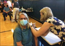 ??  ?? Debbie Sparks smiles beneath her mask as Trish Stephan administers her vaccine shot at Friday's clinic.