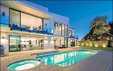 ?? Mark Singer ?? SINGER-SONGWRITER John Legend and his wife, model Chrissy Teigen, paid $14.1 million for a remodeled contemporary-style house with five bedrooms and eight bathrooms. The home's amenities include a pool.