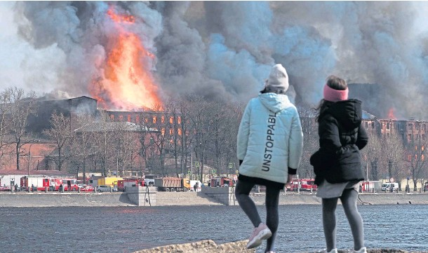 ??  ?? INFERNO: Two bystanders watch the flames engulf the four-storey business centre in St Petersburg, Russia's second-largest city.