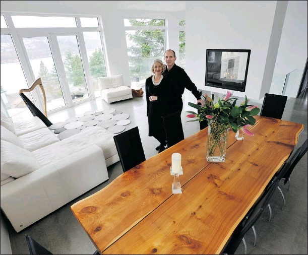 ?? IAN SMITH/ PNG ?? Zoe and Gaetan Royer in their Port Moody home, the dining table made from trees that were on the property before construction.