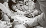 ?? Godofredo A. Vásquez / Staff photographer ?? Medical intern Gabriel Cervera, left, and medical staff work to establish a venous line into a patient.