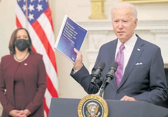 """?? AFP ?? Mensaje. El presidente Biden muestra ayer a los periodistas un ejemplar de la """"Estrategia Nacional"""" para combatir al coronavirus en EE.UU."""