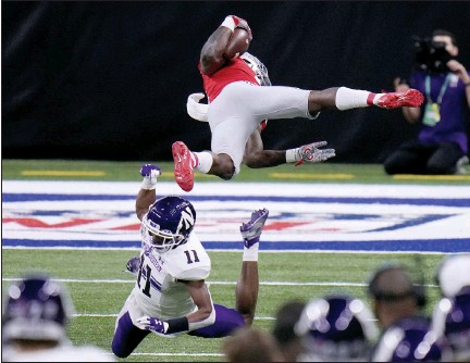 ?? PHOTOS BY AJ MAST — THE ASSOCIATED PRESS ?? Ohio State running back Trey Sermon, top, is sent flying by Northwestern defensive back A.J. Hampton (11) during the first half of the Big Ten championship on Saturday in Indianapolis.