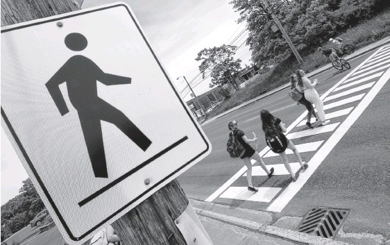 ?? KEITH GOSSE • THE TELEGRAM ?? Pedestrians use a crosswalk on a four-lane section of the Conception Bay Highway near the Manuels River Interpretation Centre Friday afternoon.