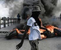 ??  ?? A protester demanding justice for slain President Jovenel Moïse stands near a burning barricade in Cap-Haïtien on Thursday.