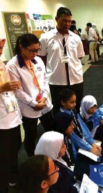 ??  ?? Schoolchildren listening to mentors at the UTM booth. The cover picture shows a UPSI physics department lecturer (right) demonUiTM strating an experiment using the Pascal lab kit.