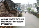 ??  ?? A man wades through floodwater in eastern Philippines