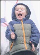 ?? PHOTO BY TOM MCCALL ?? Full of exuberance at the sight of 15 cop cars, fire trucks, and a big 18 wheeler full of wreaths, a child waves his flag.