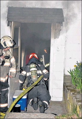 ?? DAVID BRYCE / SENTINEL & ENTERPRISE ?? Firefighte­rs from the Lancaster Fire Department enter the apartment house at 217 White Pond Road Tuesday night.