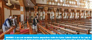 ?? — AFP ?? BAGHDAD: A nun and caretakers finalize preparations inside the Syrian Catholic Church of Our Lady of Deliverance in the Karrada district of Iraq's capital Baghdad yesterday amidst preparations ahead of the pontiff's visit.