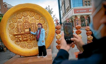 ?? AP ?? A woman poses for a photograph with a giant statue of a piece of Uyghur nang bread at the International Grand Bazaar in Urumqi in Xinjiang, as seen during a government organised trip for foreign journalists last month.