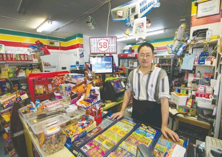 ?? ARLEN REDEKOP ?? Store owner Jian Li Li stands inside Helen's, his corner store in Kitsilano which is under threat of closure after more than 100 years.