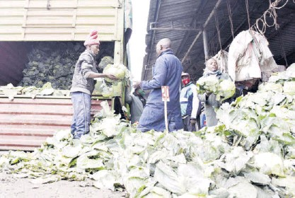 ?? / MERCY MUMO ?? Ven­dors off­load cab­bages from a lorry at Muthurwa mar­ket on Tues­day