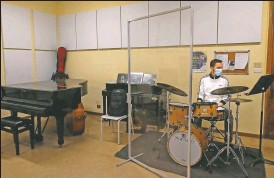 ??  ?? Andrea Lopalo wears a mask and plays the drums behind a transparent panel during a lesson at the Giuseppe Verdi Music Conservatory.